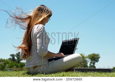 Happy young girl smiling and working on a laptop outdoors