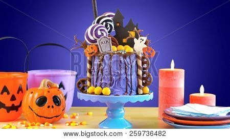 On Trend Halloween Candyland Novelty Drip Cake In Colorful Purple Party Setting.