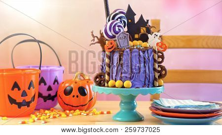 On Trend Halloween Candyland Novelty Drip Cake In Colourful Party Setting.