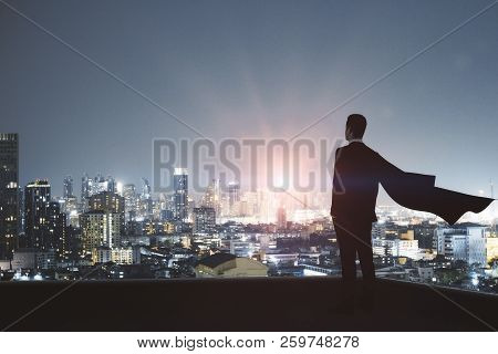 Young Backlit Super Hero Businessman On Rooftop With Night City View. Leadership And Confidence Conc