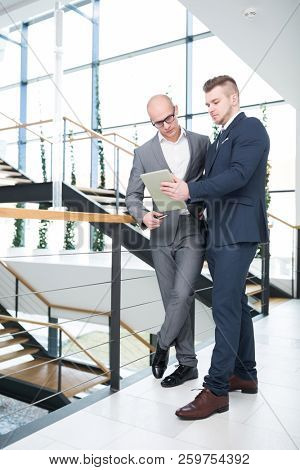 Full length of confident businessmen discussing over tablet computer in office