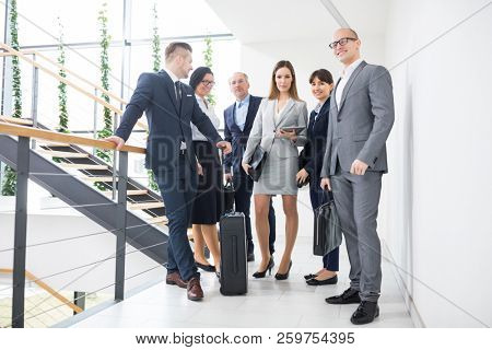 Full length of confident business team standing together on corridor in office
