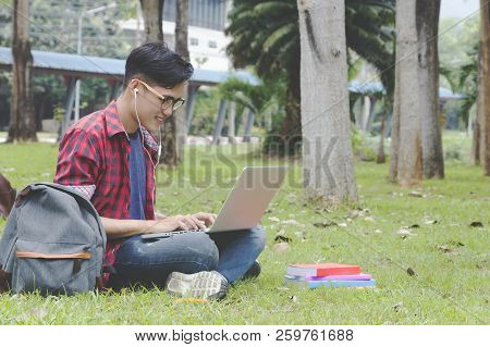 Asian Attractive Male Student Thinking About Coursework Strategy Sitting In University Garden With L