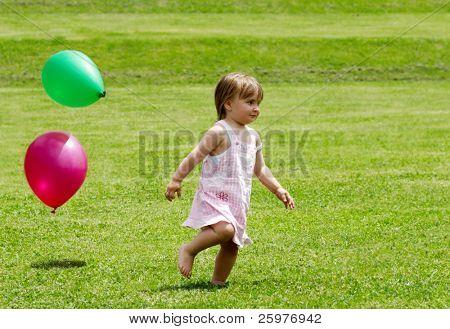 La niña corriendo en un pasto con globos