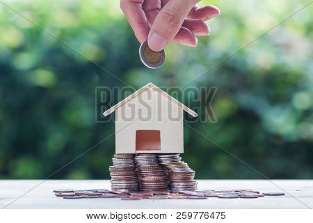 Saving Money, Home Loan, Mortgage, A Property Investment For Future Concept : A Man Hand Putting Coi