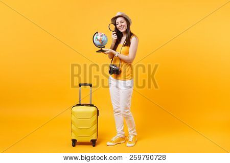 Tourist Woman In Summer Hat Looking Through Loupe On Globe, Choice Country Isolated On Yellow Orange