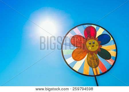 Children's Pinwheel In Windy Weather Against The Blue Sky On A Sunny Day