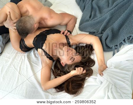 Young couple being intimate kissing on bed. Sensual lovers making love in bedroom. poster