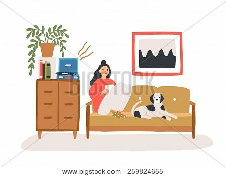 Young Woman Sitting On Cozy Sofa With Her Dog, Drinking Tea Or Coffee And Listening To Playing Vinyl