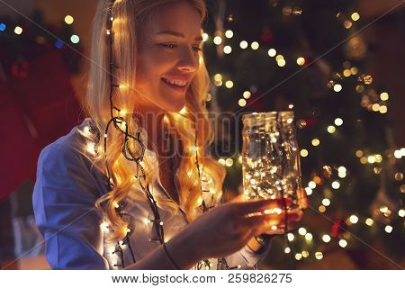 Beautiful Woman Next To A Nicely Decorated Christmas Tree, Holding Bunch Of Christmas Lights, Settin