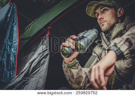 Caucasian Hunter Spotting Wildlife From His Tent In Remote Place.