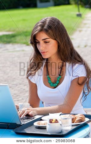 A young attractive woman sitting in a cafe with a laptop