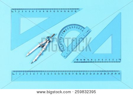 Transparent Rulers, Protractor And Compasses On Blue Surface