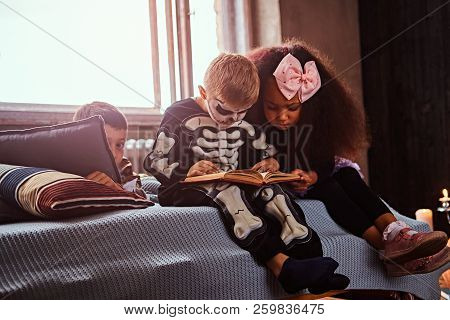 Three Multiracial Kids In Scary Costumes Reading Horror Stories While Sitting On Bed In An Old House