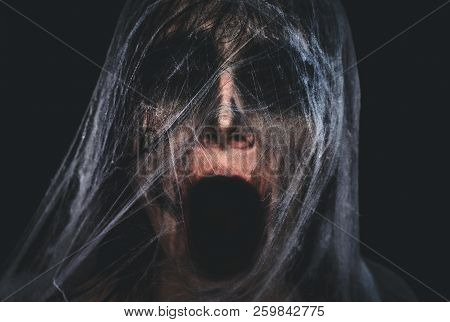 Screaming Creepy Character Covered With Spiderweb On Black Background. Halloween Spooky Creature Por