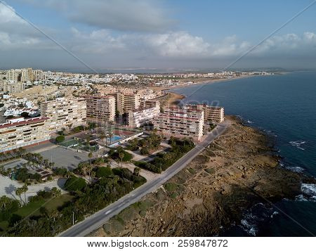 Aerial photography La Mata residential district, Torrevieja townscape. Rocky coast blue Mediterranean Sea top above view. Famous place for travellers and vacationers. Alicante province, Costa Blanca. Spain poster