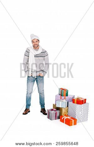 Handsome Man In Scarf And Hat Standing With Hands In Pockets Near Gift Boxes And Smiling At Camera I