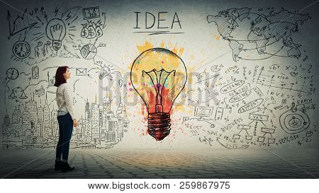 Side View Of A Pensive Young Woman Looking At The Wall With Colorful Light Bulb And Business Sketch.