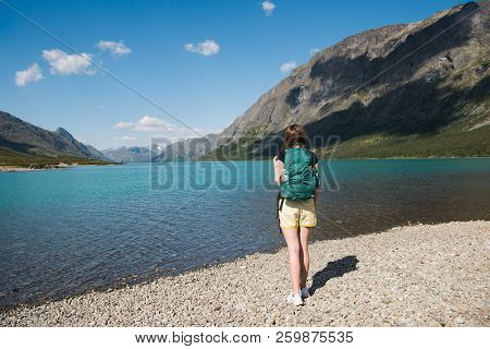 Back View Of Young Woman With Backpack Looking At Gjende Lake, Besseggen Ridge, Jotunheimen National