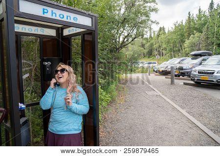 July 30 2018 - Denali Alaska: Happy Laughing Blonde Woman Talks On A Landline Phone Inside Of A Tele