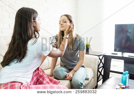 Woman Applying Make-up On Friend's Face In Sitting Room