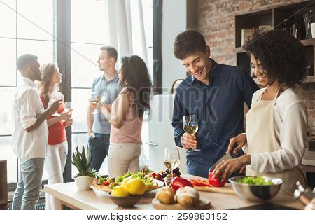 Home Party. Multiethnic Couple Preparing Dinner And Drinking Wine With Friends In Kitchen