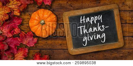 A Rustic Wooden Background With Autumn Foliage - Happy Thanksgiving