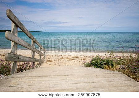 Path To The Beach. Wooden Ramp Leads To A Wide Sandy Beach With A Blue Water Horizon On A Sunny Sand