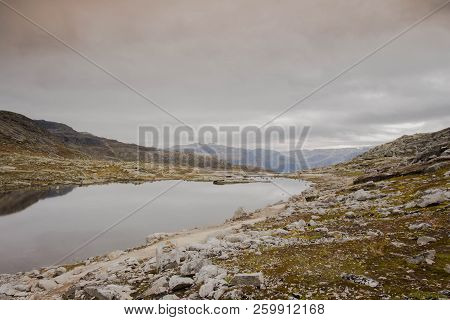 Rugged Dramatic Mountain Landscape In Norway Cloudy Dramatic Day Autumn With A Calm Lake Beauty