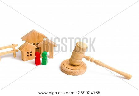 Wooden Apartment House With People, Keys And A Judge Hammer On A White Background. The Concept Of La