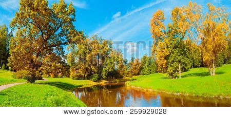 Autumn landscape scene - autumn trees near the river in sunny autumn October park lit by sunlight. Panorama of autumn park in sunny weather