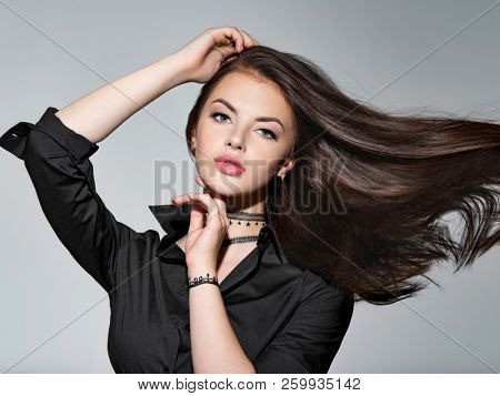 Young woman with long straight hair - at studio. Portrait of an attractive brunette girl. Fashion model wears black shirt. Sexy female model
