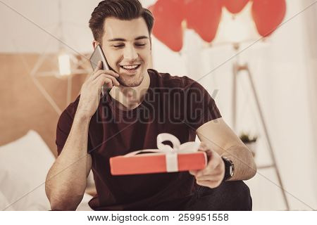 Contended Young Man Preparing Present For His Wife While Sitting In Living Room