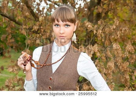 Portrait of the beautiful young girl against green foliage