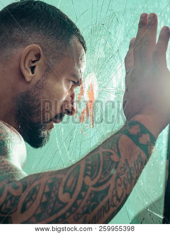 Man Latin With Muscular Body Looks Through A Broken Window. Brutal Handsome Man With Tattooed Body.
