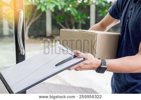 Woman Courier Holding A Parcel Shipping Mail Appending Signature Signing Delivery Note After Receivi