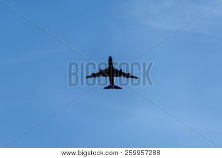 Silhouette Of A Passenger Airplane On A Background Of An Empty Blue Sky. Aviation, Passenger Transpo