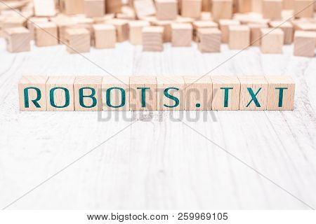 The Word Robots.txt Formed By Wooden Blocks On A White Table