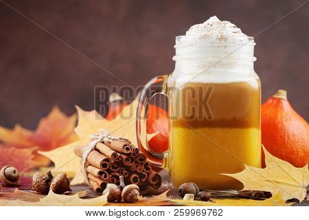 Pumpkin Spiced Latte Or Coffee In Glass Jar Decorated Leaves On Brown Table. Autumn, Fall Or Winter