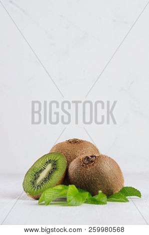 Ripe Fleshy Green Kiwi With Juicy Slice, Young Leaves On Soft Light White Table, Vertical. Tropical