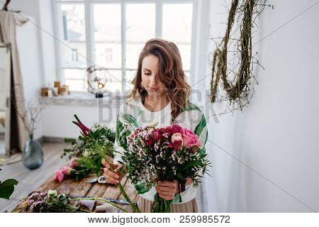 A Girl Florist Makes A Bouquet In A Light Studio On A Wooden Table.
