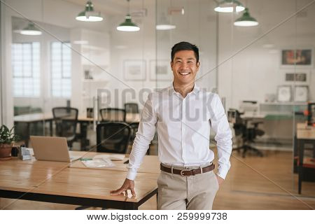 Young Asian Businessman Standing In An Office Smiling Confidently
