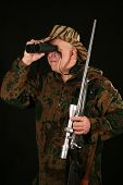 a hunter looks through his binoculars against a black background poster