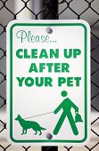 "a ""please clean up after your pet"" sign in a park poster"