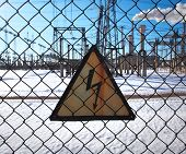 High-voltage transformer substation behind barbed-wire chain-link fence with Danger High Voltage sign. poster