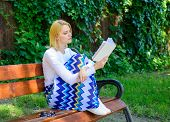 Literary critic. Lady pretty bookworm busy read book outdoors sunny day. Woman concentrated reading book in garden. Woman prepare review about bestseller. Girl sit bench read book nature background poster