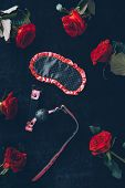 top view of eye mask, gag and red roses on black poster