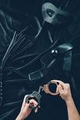 cropped shot of woman holding handcuffs, leather whip, gag and mask on black fabric poster