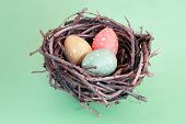 Three speckled eggs in bird's nest over green background poster