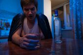 Alcohol addicted man sitting in kitchen at home. Drunken male adult drinking glass of vodka. poster